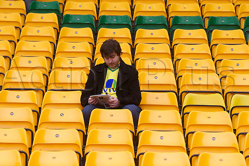 20.04.2014.  Norwich, England.  Norwich fan reading the program before the Barclays Premier League match between Norwich City and Liverpool from Carrow Road.