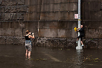 Jennifer Warren (R) poses for a photograph holding on to a post in a rain water flooded section of 12th Avenue in Hamilton Heights, New York City, NY, USA shortly after tropical storm Irene passed over the city, 28 August 2011.