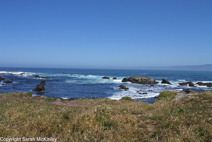 A vista of the blue waters of the Pacific Ocean, as seen from a grassy bluff, with rock formations in the water. At MacKerricher State Park near Fort Bragg in Mendocino County in Northern California.
