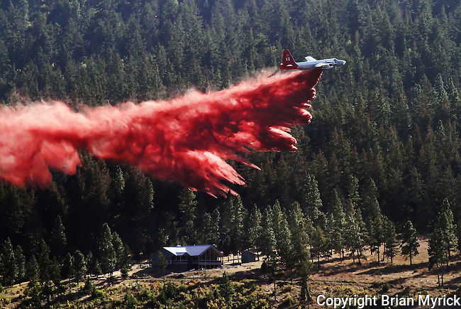 A firefighting aircraft drops fire retardant along a ridge near the Swauk valley area northeast of Cle Elum, in an effort to defend homes from the Taylor Bridge Fire, Tuesday, Aug. 14, 2012. (Brian Myrick / Daily Record)