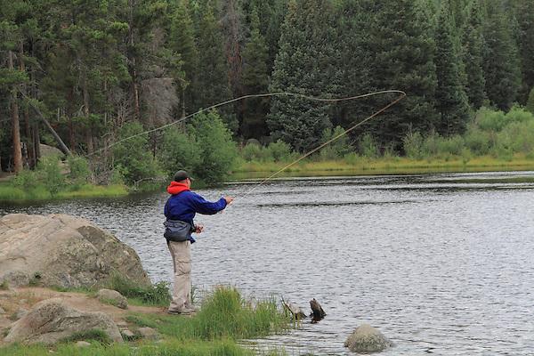 Man fly fishing at Sprague Lake in Rocky Mountain National Park, near Estes Park, Colorado.