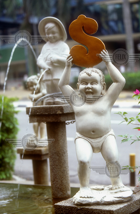 A fountain statue holding a dollar sign.