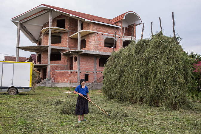 Old woman getting the hay in front of a new family house, Oas area.