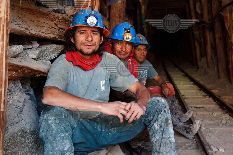 Miners sit at the entrance of a gold mine in the village of Cuatro Horas in the department of Arequipa.