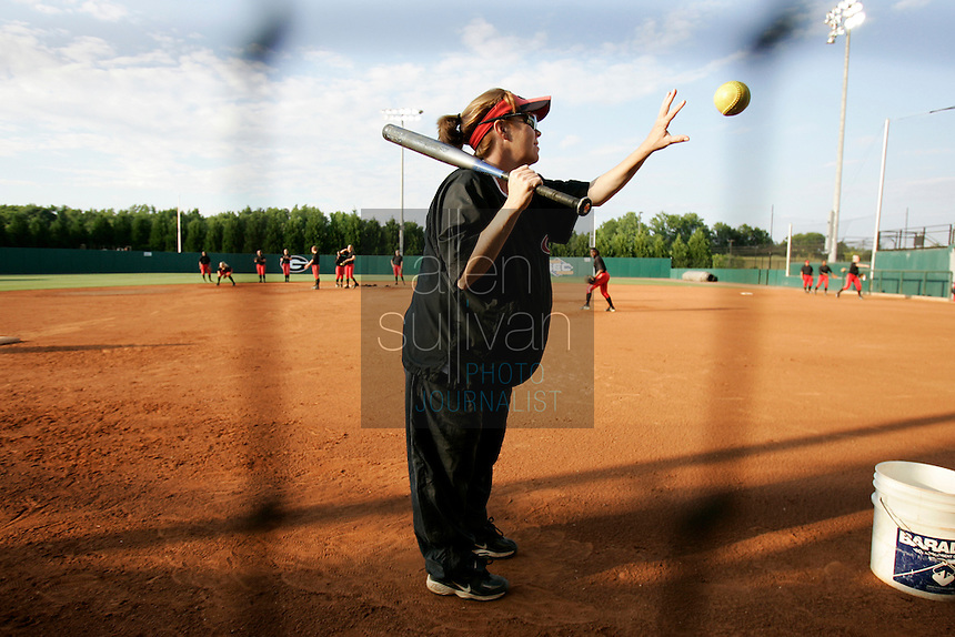 UGA softball coach and mother of two Lu Harris-Champer catches a ball while hitting grounders to the team during practice in Athens, Ga. on Wednesday, May 27, 2006. She is due to give birth to another daughter next week. Her husband, Jerry Champer, is an assistant coach for the UGA swimming team.