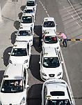 Line of white taxis queuing outside Malaga airport, Spain