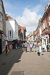 People shopping in busy pedestrianised street in Winchester, Hampshire, England, UK