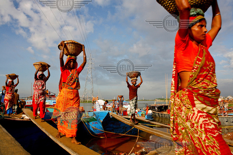 Male and female labourers carrying basket loads of building agregate from a barge onto the shore.