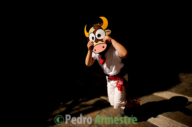 A child plays during San Fermin Festival bull run, on July 12, 2012, in Pamplona, northern Spain. The festival is a symbol of Spanish culture that attracts thousands of tourists to watch the bull runs despite heavy condemnation from animal rights groups. (c) Pedro ARMESTRE