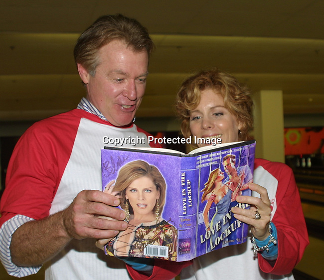 """Guiding Light's Liz Kiefer (Blake) and Jerry verDorn (Ross) look at her character's book at the """"Bloss"""" Bowling Event during the Guiding Light weekend on October 15, 2005 at the Port Authority, NY (Photo by Sue Coflin)"""