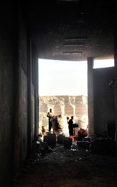 """De jeunes coptes trient de gros sacs de déchet dans un entrepôt de """"Garbage city"""", bidonville de la banlieue du caire, peuplé en grande majorité de chrétiens recyclant les déchets de la ville pour gagner leur vie."""