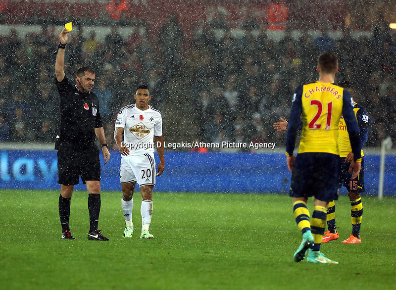 Sunday 09 November 2014 <br /> Match referee Phil Dowd (L) shows a yellow card to Calum Chambers of Arsenal (R) for his foul against Jefferson Montero of Swansea (C)<br /> Barclays Premier League, Swansea City FC v Arsenal City at the Liberty Stadium, Swansea, Great Britain. EPA/Dimitris Legakis