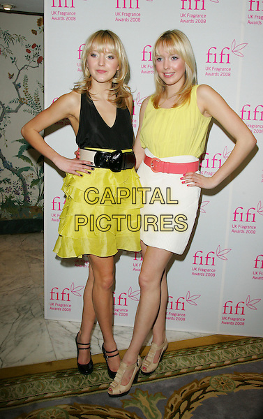 SAMANTHA & AMANDA MARCHANT .Attending the FIFI UK Fragrance Awards 2008 at the Dorchester Hotel, Park Lane, London, England, April 23rd 2008.full length samanda sam big brother twins sisters yellow fluro ruffle tiered skirt top black vest belt red white Topshop beige shoes double strap mary janes hands on hips.CAP/ROS.©Steve Ross/Capital Pictures