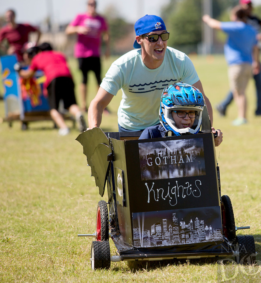 NWA Democrat-Gazette/JASON IVESTER<br /> Christopher Hyatt pushes and Daniela (cq) Reyes, both of Bentonville, steers their team cart on Wednesday, Sept. 21, 2016, during a race at Phillips Park in Bentonville. Five teams built and raced their carts as part of a quarterly team-building exercise for employees in the Wal-Mart Supplier and Contract Management for U.S. Realty team.