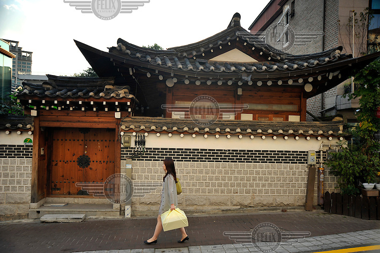 Woman walking past a traditional wooden home in the Bukchon Hanok district of central Seoul.
