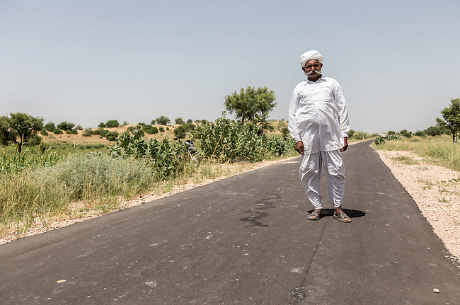 04 September, 2013, Jodhpur, Rajasthan INDIA : Village elder Bajpal Singh on the new road at Boongari Village, District Jodphur and speaking about  how the Pradhan Mantri Gram Sadak Yojana program (PMGSY) has made a difference to their lives in Rajasthan. The roads have allowed them to move in medical supplies and increased the village income by more efficiently getting crops to market. It also means the women don't have to hand mill the grain but can transport it to a local mill. PMGSY is a nationwide plan in India to provide good all-weather road connectivity to unconnected villages.<br /> It is under the authority of the Ministry of Rural Development and was begun on 25 December 2000 It is fully funded by the central government and implemented in conjunction with the World Bank<br /> The goal was to provide roads to all villages  with a population of 500 persons and above by 2007, in hill states, tribal and desert area villages with a population of 250 persons and above by 2007. Picture by Graham Crouch/World Bank