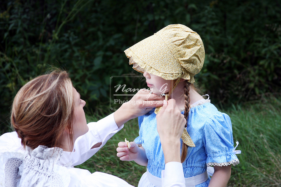 A woman tying the bonnet on a little girl
