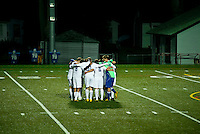 Soccer team huddles before match.