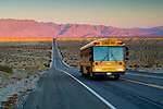 School bus on long straight two lane desert road at sunrise, Anza Borrego Desert State Park, San Diego County, California