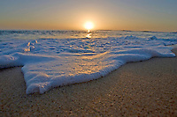 Frothy white-water washes along a sandy beach on the Leeward coast of Oahu, Hawaii.