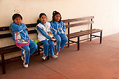 Arequipa, Peru. A. Antoniano (public elementary and secondary school). Portrait of three students (girls, elementary-school aged, Peruvian).on a bench in breezeway at their school. No MR. ID: AL-peru.