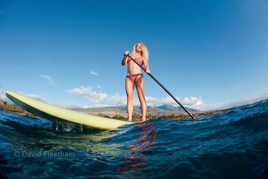 Surf instructor Tara Angioletti on a stand-up paddle board off Canoe Bearch, Maui. Hawaii.  The West Maui Mountains are in the background. Image is model released.