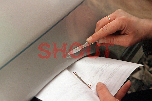 Scenes of crime officer scraping paint from the wing of a car suspected to be involved in a road traffic accident. The paint will be taken away and analysed in a police laboratory. This image may only be used to portray the subject in a positive manner..©shoutpictures.com..john@shoutpictures.com