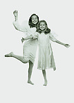 b/w portrait of two young girls playfully dancing, smiling, in little angel outfits