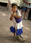 Village near Tegucigalpa, Honduras. Hondurian girl in white dress playing in tree.