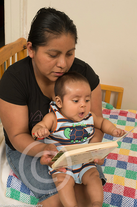 3 month old baby boy with mother, looking at board book interested expression