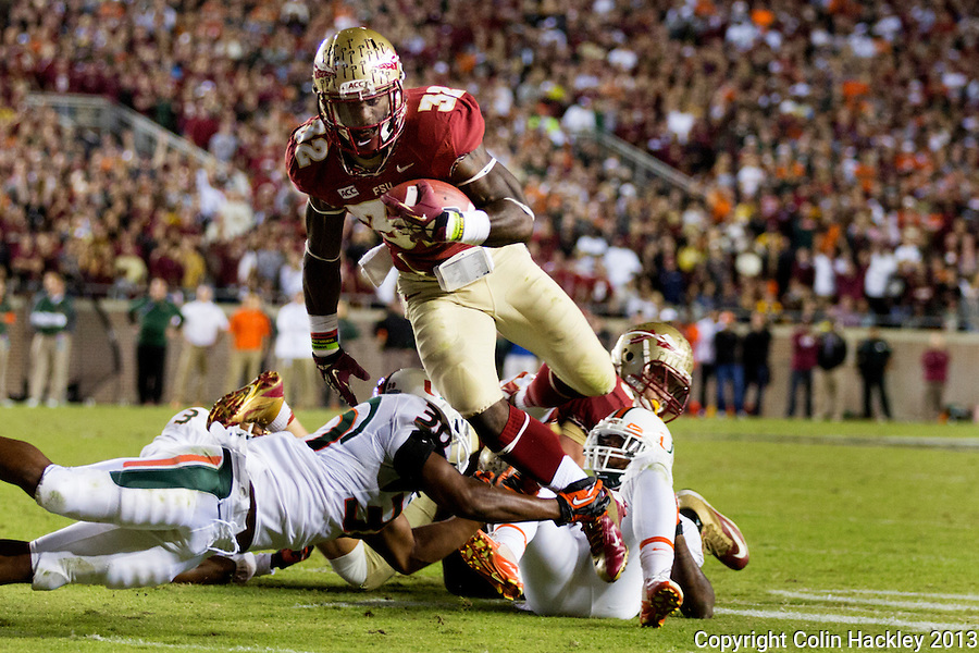 TALLAHASSEE, FL 11/2/13-FSU-MIAMI110213CH-Florida State's James Wilder, Jr. runs out of a tackle by Miami's AJ Highsmith enroute to a touchdown during second half action Saturday at Doak Campbell Stadium in Tallahassee. The Seminoles beat the Hurricanes 41-14.<br /> COLIN HACKLEY PHOTO