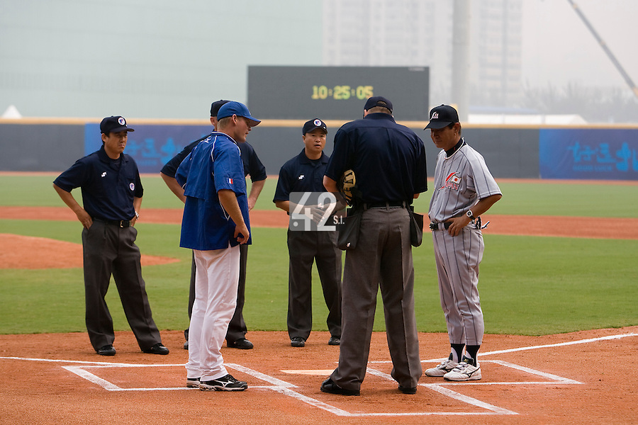 19 August 2007: Team managers Jeff Zeilstra from France (left) and Senichi Hoshino from Japan (right) listen to home plate umpire David Kulhanek prior to the Japan 4-3 victory over France in the Good Luck Beijing International baseball tournament (olympic test event) at the Wukesong Baseball Field in Beijing, China.
