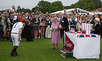 Cartier Queen Cup winner Thai Aiyawatt Srivaddhanaprabha (King Power Foxes) bows as he collects the Cup from Her Majesty the Queen and Arnaud M. Bamberger, Executive Chairman during the Cartier Queens Cup Final match between King Power Foxes and Dubai Polo Team at the Guards Polo Club, Smith's Lawn, Windsor, England on 14 June 2015. Photo by Andy Rowland.