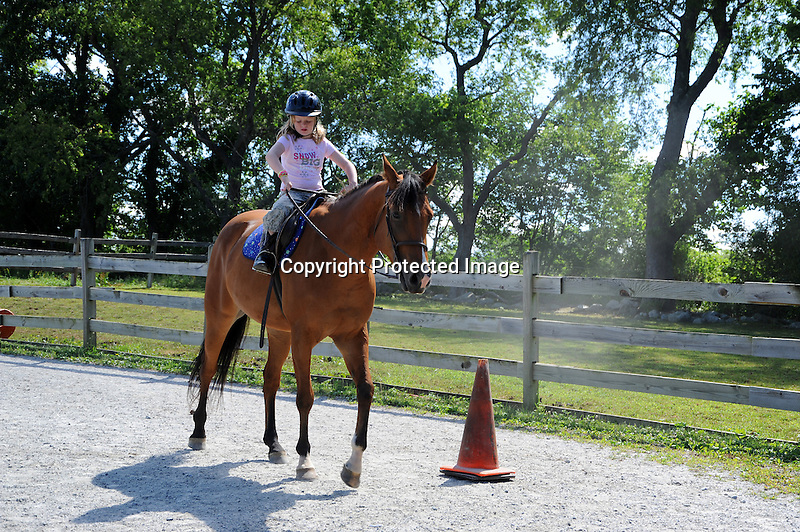 Young girl having a horseback riding lesson at the stable USA