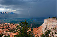 730750181 a summer monsoon rainstorm with lightning strikes passes in the distance in this view from bryce point in bryce canyon national park utah united states