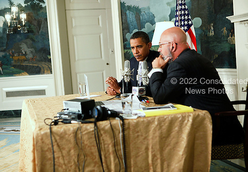 Washington, DC - August 20, 2009 -- United States President Barack Obama (L) speaks as he is interviewed by radio show host Michael Smerconish (R) during a live broadcast from the Diplomatic Reception Room of the White House August 20, 2009 in Washington, DC. Other than being interviewed by Smerconish, Obama also took questions from a few call-in audience members.  .Credit: Alex Wong / Pool via CNP
