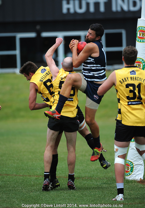 Ben Hick takes a mark during the Wellington Australian Rules Football National Provincial Championship final match between the Wellington Tigers (black and yellow) and Auckland Buccaneers (blue and white) at Hutt Park, Wellington, New Zealand on Saturday, 6 December 2014. Photo: Dave Lintott / lintottphoto.co.nz