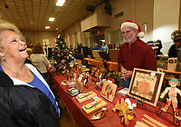 NWA Democrat-Gazette/FLIP PUTTHOFF<br /> LOOKING A LOT LIKE CHRISTMAS<br /> John Brach, a woodcarver, sports a Santa hat while helping a customer on Saturday Nov. 11 2017 at the Bella Vista Christmas Bazaar. Dozens of vendors sold holiday items and served refreshments at the event held at Riordan Hall in Bella Vista.