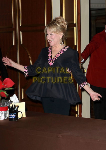 "BETTE MIDLER.Signs copies of her book ""The Saga of Baby Divine"" in front of the Colosseum at Caesar's Palace Resort Hotel and Casino, Las Vegas, Nevada, USA, .6th January 2010..half length black top pink pattern trim sleeves v-neck hands .CAP/ADM/MJT.©MJT/Admedia/Capital Pictures"
