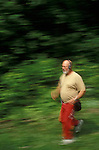 Man with portable music device running in forest