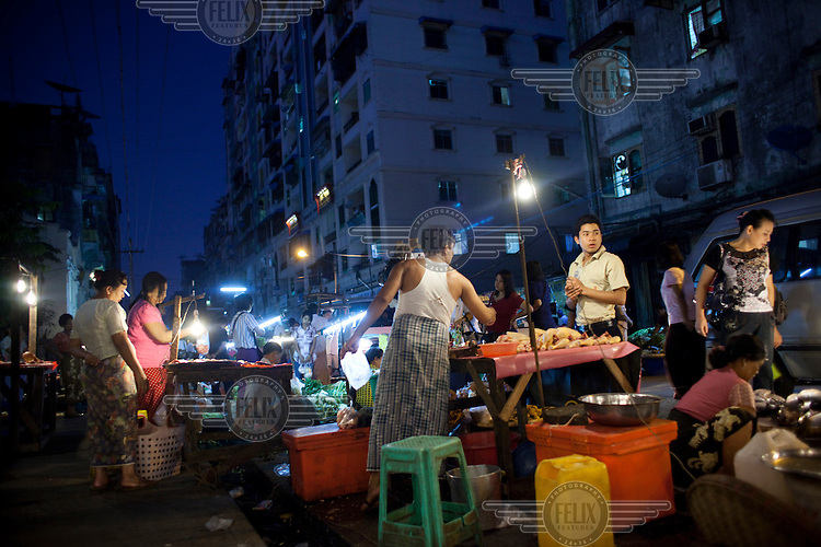 A man buys chicken at a street market in Yangon.