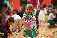 NWA Democrat-Gazette/J.T. WAMPLER  Ryleigh Kenaga, 3, of Fayetteville hauls her packet full of Easter Eggs Sunday March 25, 2018 during the annual Donald W. Reynolds Boys and Girls Club Easter at the Club event. Children got to scoop up 16,000 eggs and there was face painting and carnival games. The event was moved inside due to rainy weather.
