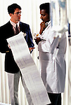 hospital administrator and doctor reviewing long printout