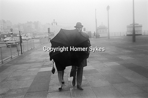 Middle aged couple walking during traditional English seaside bad weather Brighton sea front, Sussex England