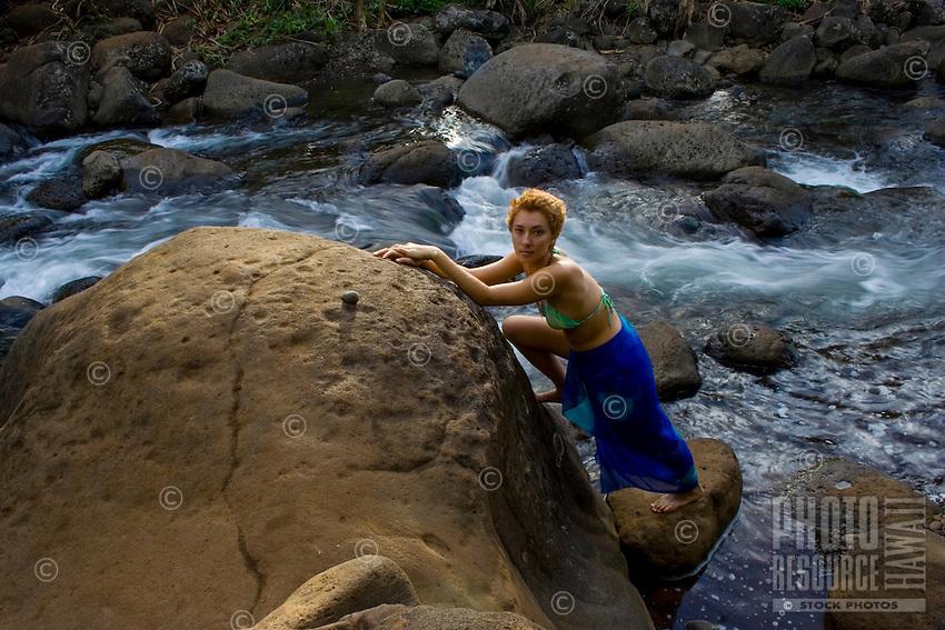 A young woman in a green bikini and blue pareo steadies herself on rocks next to Hanakapi'ai Stream, Na Pali Coast, Kaua'i.