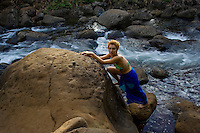 A young woman in a green bikini and blue pareo steadies herself on rocks next to Hanakapi'ai Stream, Na Pali Coast, Kaua'i.