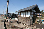 Mar. 13, 2011 - Kita-Ibaraki, Japan - Two vehicles are shown piled up next to a small storage building two days after the 8.9 magnitude earthquake struck followed by a tsunami that hit the north-eastern region. The death toll is currently unknown with casualties that may run well into the thousands.