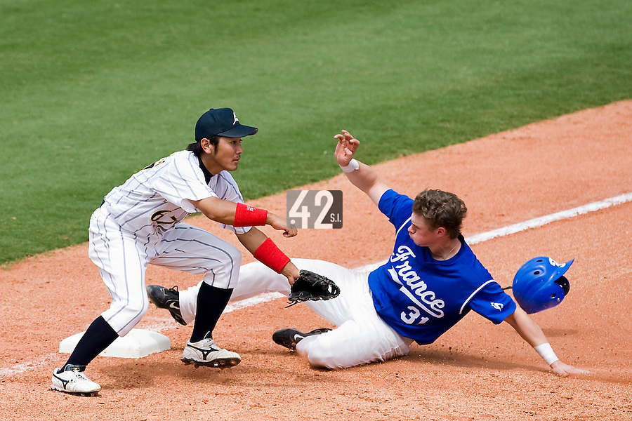 22 August 2007: Anthony Cros slides safely into third base over third base #67 Jun Ohtsuka during the Japan 9-4 victory over France in the Good Luck Beijing International baseball tournament (olympic test event) at west Beijng's Wukesong Baseball Field in Beijing, China.