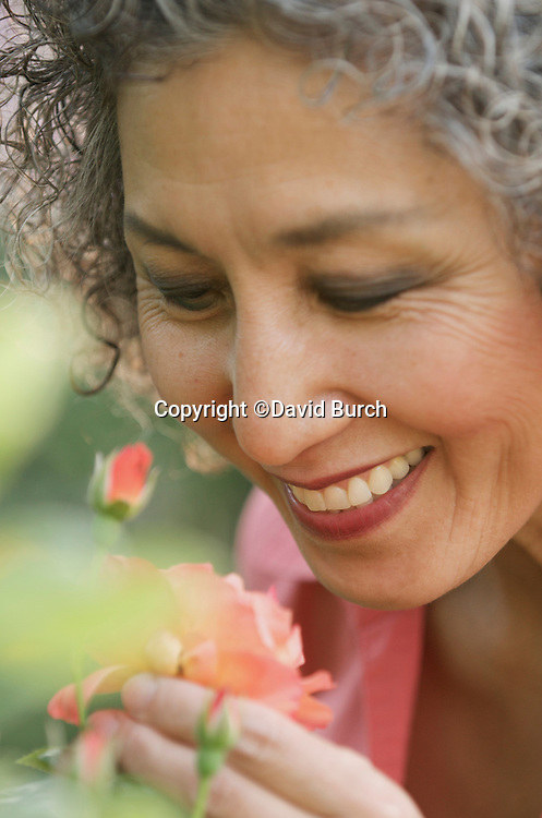 Asian woman smiling and smelling rose