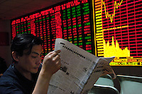 A man reads a newspaper in front of index board of a stock exchange in Beijing, China. Chinese share prices broke through the psychologically important 4000-mark for the first time ever last week and dealers said the sustained Chinese advance is being driven by massive inflows of fresh funds as smaller investors take their money out of low-return bank deposits and punt on stocks..16 May 2007